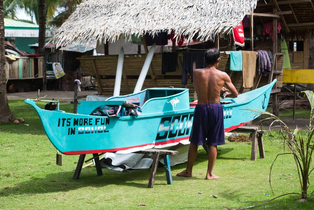 Pamilacan-Island_Fischer-putzt-sein-Boot_SOMEWHERE-ELSE