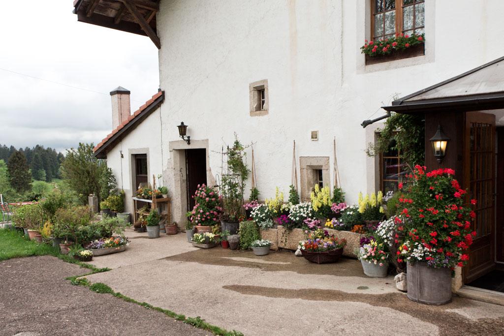 Schweiz Jura – Auberge de Mont Cornu – Blumen vor dem Haus | SOMEWHERE ELSE