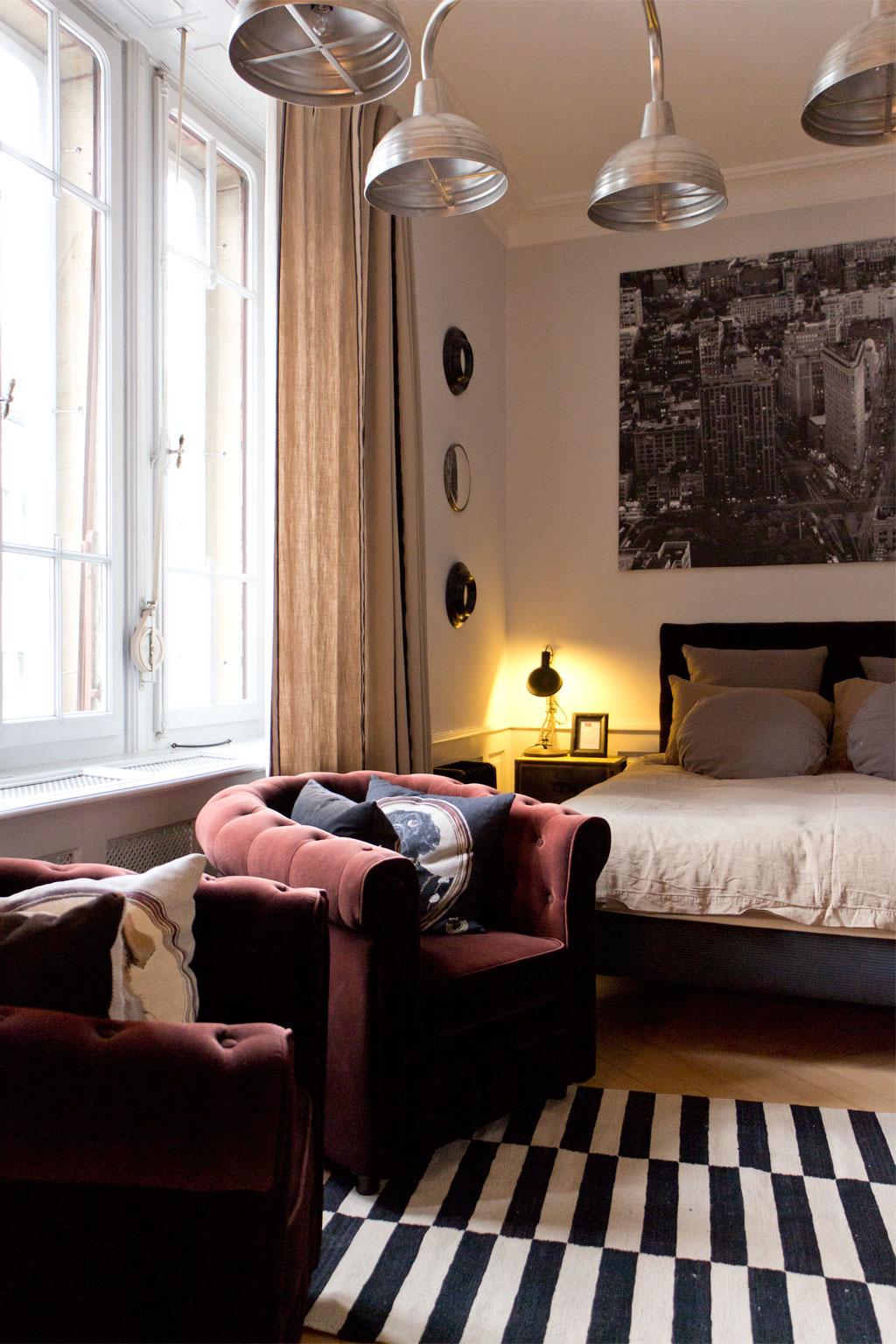 Schweiz Jura – Passion d'une vie – Bett und Sessel im Zimmer | SOMEWHERE ELSE